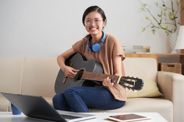 Mujer asiática, tocar la guitarra