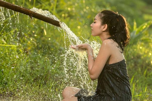 Mujer asiática tomando una ducha.