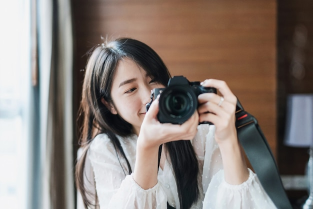 Mujer asiática tomando fotos con cámara digital sin espejo, con rostro sonriente
