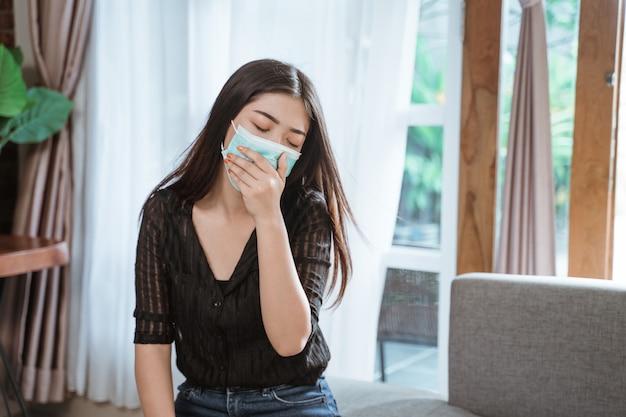 Mujer asiática tosiendo en casa
