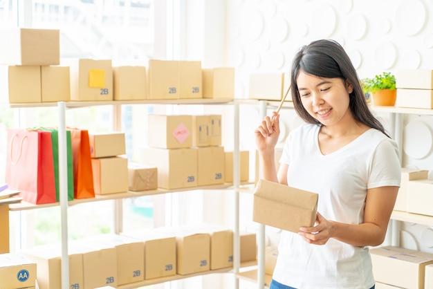 Mujer asiática trabajando en casa con cajas de embalaje