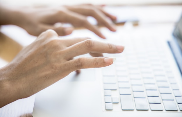 Mujer asiática trabajando en la oficina en casa mano en el teclado de cerca