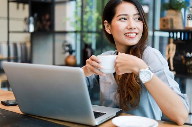Mujer asiática trabajando y tomando café en la cafetería con computadora portátil sonrisa y trabajo feliz