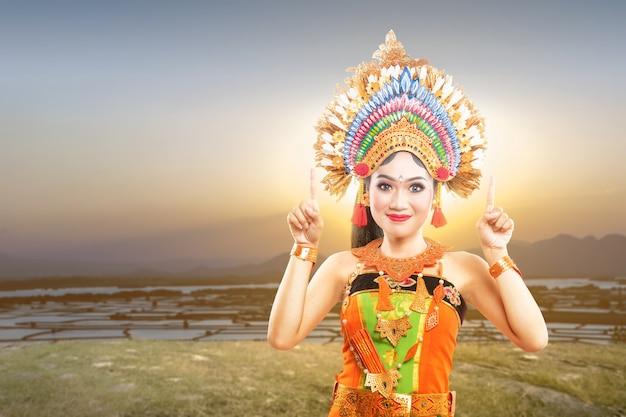 Mujer asiática con traje de danza tradicional balinesa apuntando algo al aire libre