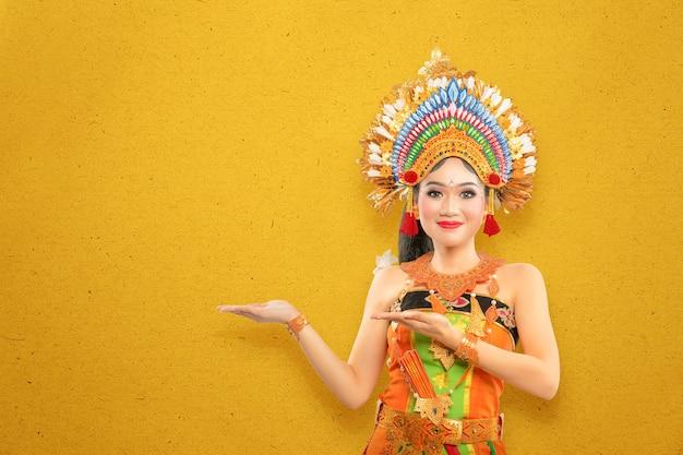 Mujer asiática con traje de danza tradicional balinesa mostrando algo