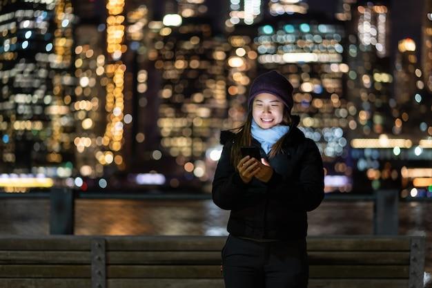 Mujer asiática en traje de invierno usando teléfono móvil inteligente con acción de sonrisa sobre la foto borrosa bokeh del paisaje urbano de nueva york