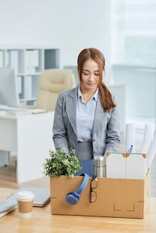 Mujer asiática en traje de negocios de pie en la oficina con sus pertenencias en caja de cartón en el escritorio
