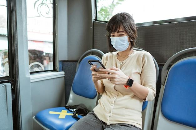 Mujer asiática en un transporte público con mascarilla durante la pandemia