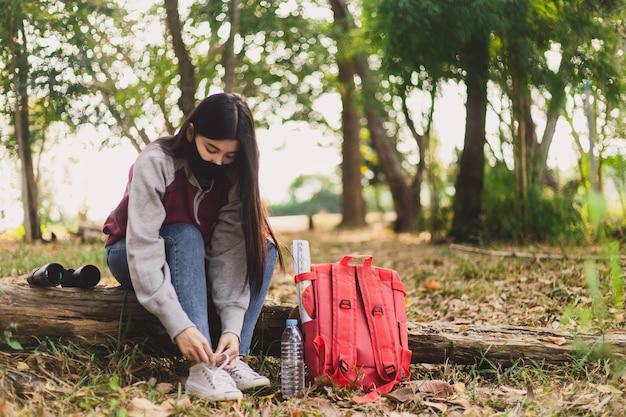 Mujer asiática turista atar los cordones de los zapatos.