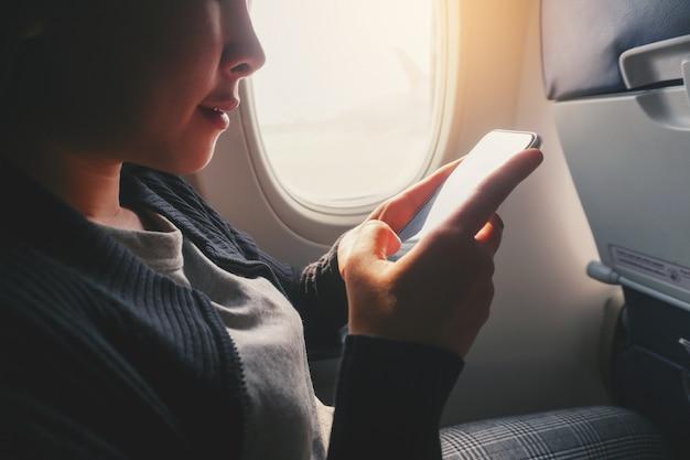 Mujer asiática turística que se sienta cerca de ventana del aeroplano y que usa el teléfono elegante durante vuelo.