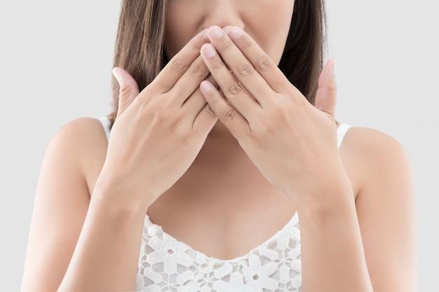 La mujer asiática usa ambas manos cerca de la boca para no comentar o rechazar