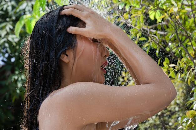 Mujer asiática, usa una ducha y se lava el cabello afuera. ella esta descansando en el resort