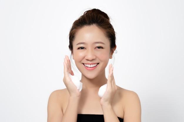 La mujer asiática usa espuma limpiadora facial para quitar el maquillaje de la cara.