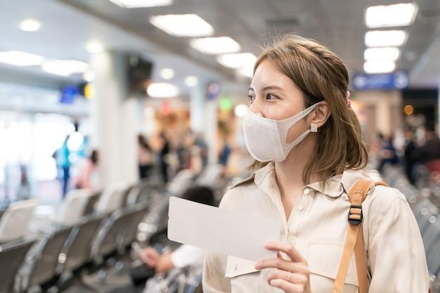 Mujer asiática usa máscaras mientras viaja, sosteniendo la tarjeta de embarque en la terminal del aeropuerto