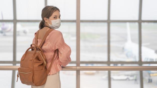 La mujer asiática usa máscaras mientras viaja a la terminal del aeropuerto. nuevo concepto de prevención de la enfermedad covid19 normal.