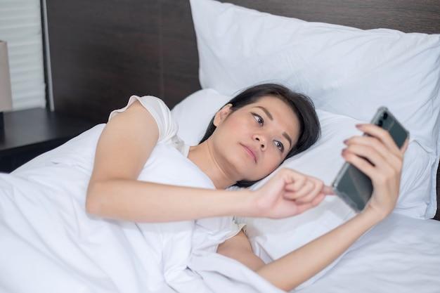 Mujer asiática usa teléfono inteligente mirando felizmente la pantalla en la cama blanca en casa