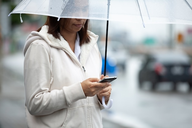 La mujer asiática está usando un teléfono inteligente, revisando la red social y sosteniendo un paraguas mientras espera un taxi en la calle de la ciudad en el día lluvioso.