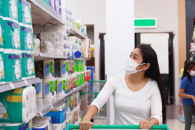 Mujer asiática usar mascarilla empujar carrito de compras en el supermercado.