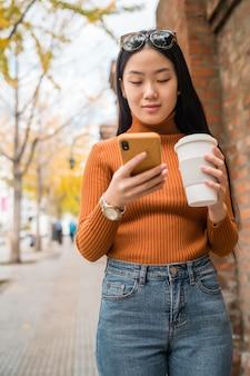 Mujer asiática utilizando su teléfono móvil.