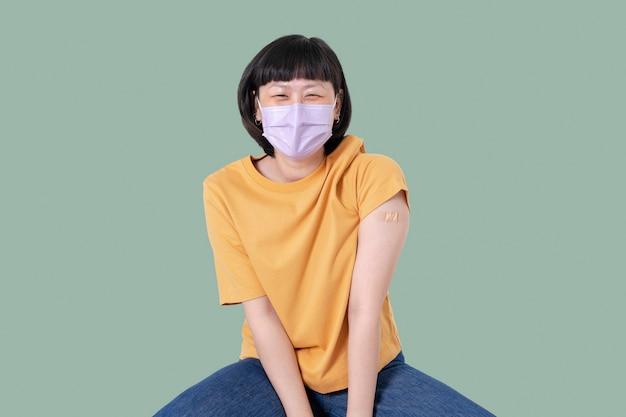 Mujer asiática vacunada presentando hombro