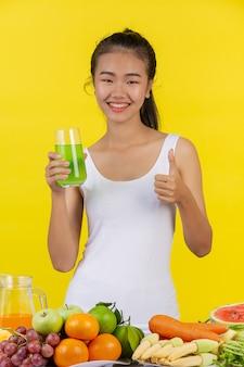 Mujer asiática con vaso de manzana con la mano derecha, y sobre la mesa hay muchas frutas.