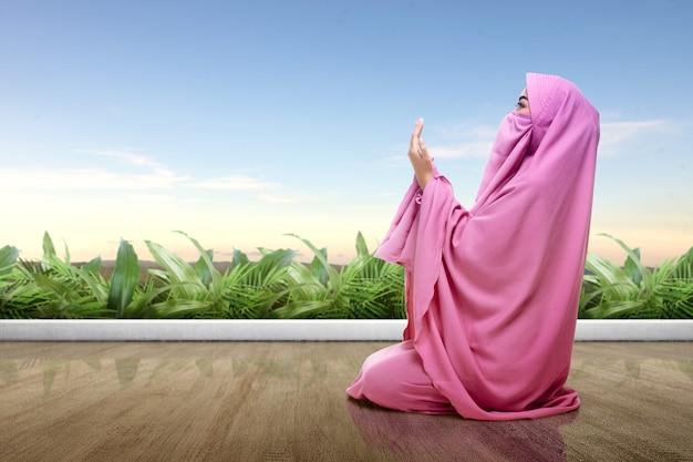 Mujer asiática en velo rosa se sienta en posición de oración