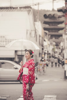Mujer asiática vestida con un kimono japonés tradicional caminando en el casco antiguo de kioto