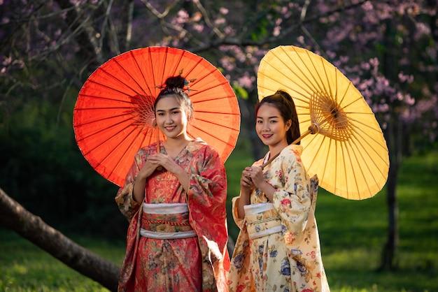 Mujer asiática vestida con kimono japonés tradicional, fondo sakura