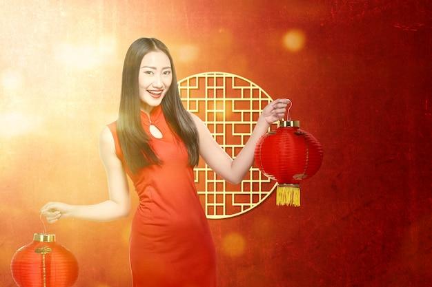 Mujer asiática en un vestido cheongsam con linterna china