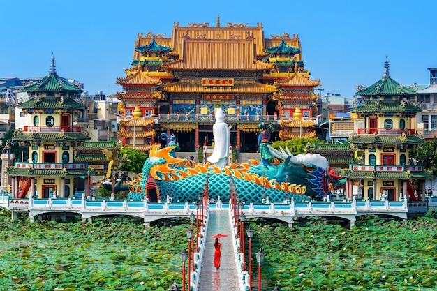 Mujer asiática en vestido chino tradicional caminando en el templo de kaohsiung, taiwán.