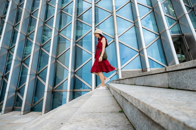 Mujer asiática en vestido rojo en edificio moderno, chica femenina con estilo de vida urbano