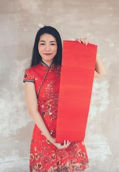 Mujer asiática en el vestido rojo tradicional de cheongsam que lleva a cabo la etiqueta roja en blanco.