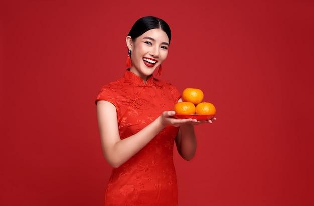 Mujer asiática con vestido tradicional cheongsam qipao con naranjas frescas aisladas en la pared roja.