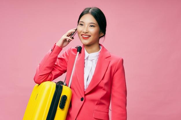 Mujer asiática viaja con una maleta en sus manos, vacaciones, estudio