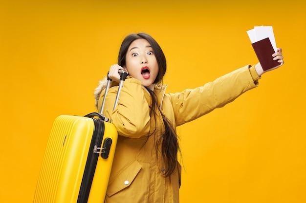 Mujer asiática viaja con una maleta en sus manos, vacaciones