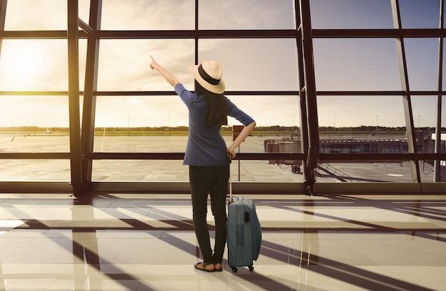 Mujer asiática del viajero con la maleta que mira puesta del sol a través de la ventana