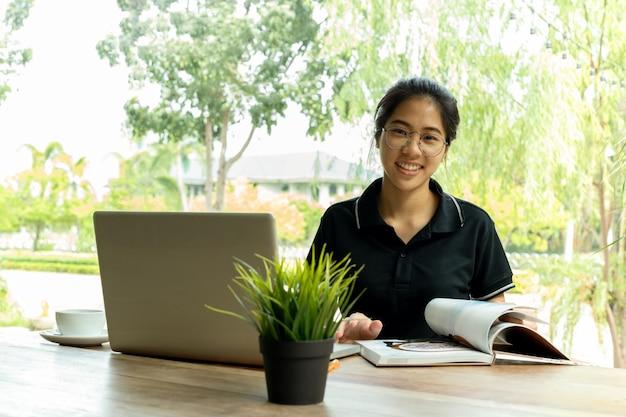 La mujer asiática con los vidrios que sonríe y abre un libro con el ordenador portátil en la tabla en café.