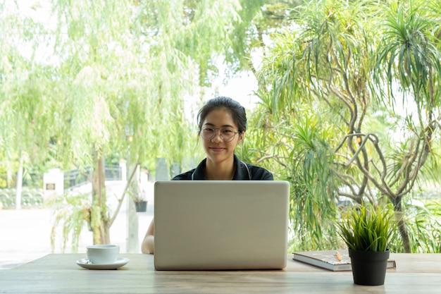Mujer asiática con los vidrios que sonríe usando el ordenador portátil con la taza de café en la tabla.