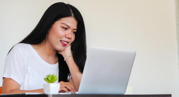 Mujer asiática viendo películas o jugando en la computadora portátil en casa en fin de semana de tiempo de relax