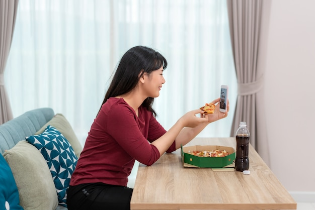 Mujer asiática virtual happy hour reunión cena y comer pizza comida en línea junto con su novio en video conferencia con tableta digital