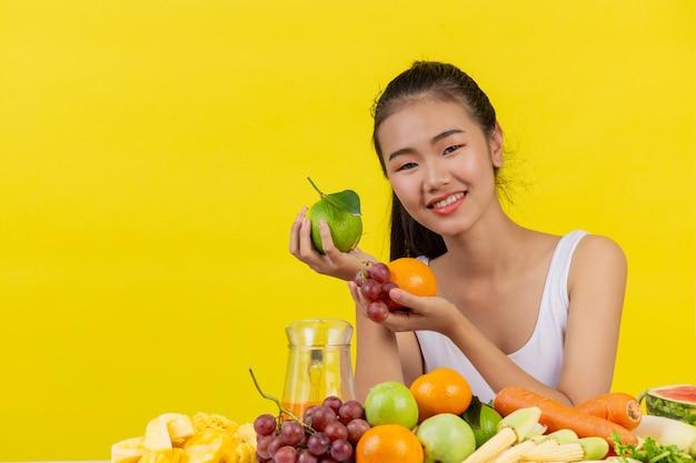 Una mujer asiática vistiendo una camiseta blanca. ambas manos sostenían fruta y la mesa está llena de varias frutas.