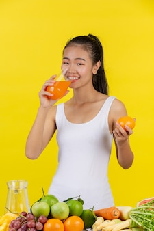 Una mujer asiática vistiendo una camiseta blanca. beber zumo de naranja y sobre la mesa hay muchas frutas.