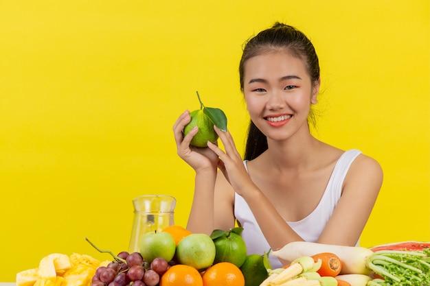 Una mujer asiática vistiendo una camiseta blanca. holdingorange con la mano derecha y en la mesa hay muchas frutas diferentes.