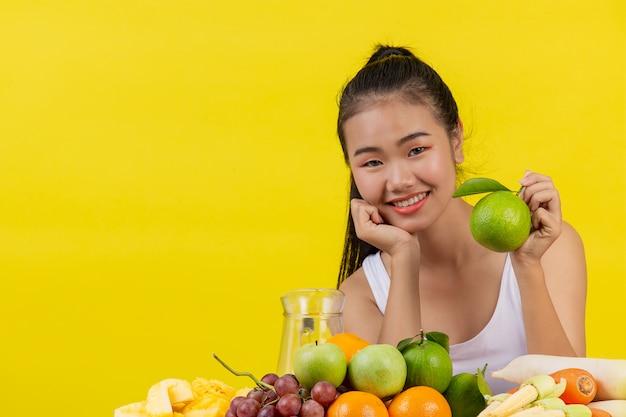 Una mujer asiática vistiendo una camiseta blanca. la mano izquierda sostiene unas naranjas verdes y la mesa está llena de muchos tipos de frutas.