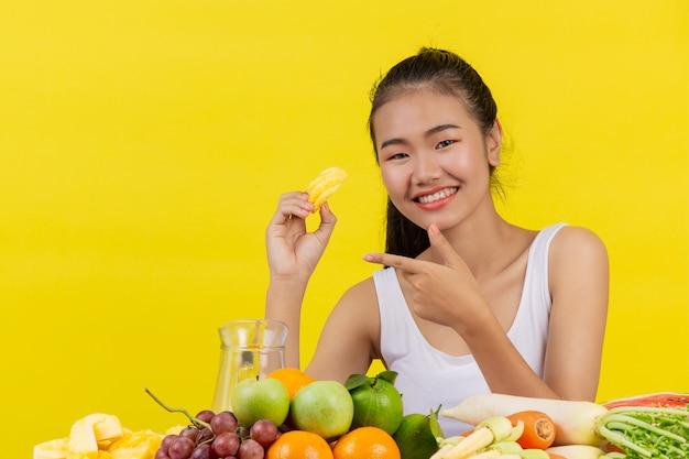 Una mujer asiática vistiendo una camiseta blanca. sosteniendo piñas con su mano derecha y sobre la mesa hay muchas frutas.