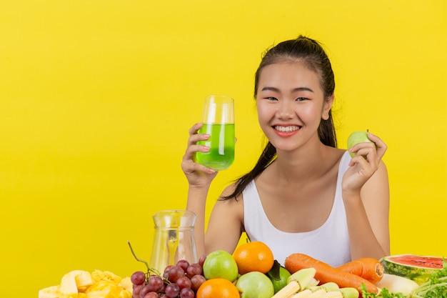 Una mujer asiática vistiendo una camiseta blanca. sosteniendo un vaso de jugo de manzana con la mano derecha sosteniendo una manzana con la mano izquierda y la mesa está llena de varios tipos de frutas.