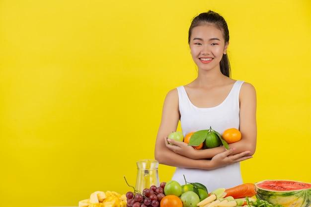 Una mujer asiática vistiendo una camiseta blanca. usa ambos brazos para sostener varias frutas. y todavía queda sobre la mesa.