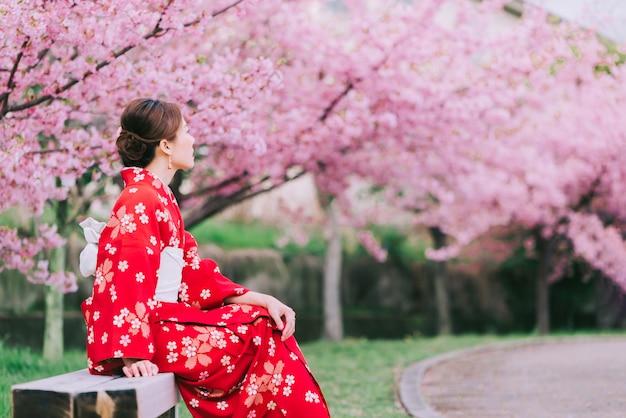 Mujer asiática vistiendo kimono con flores de cerezo, sakura en japón.