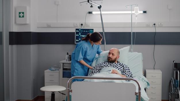 Mujer asistente médico comprobando el pulso de la frecuencia cardíaca de monitorización del hombre enfermo