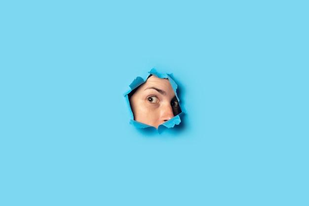 Mujer asoma y mira por el agujero en azul